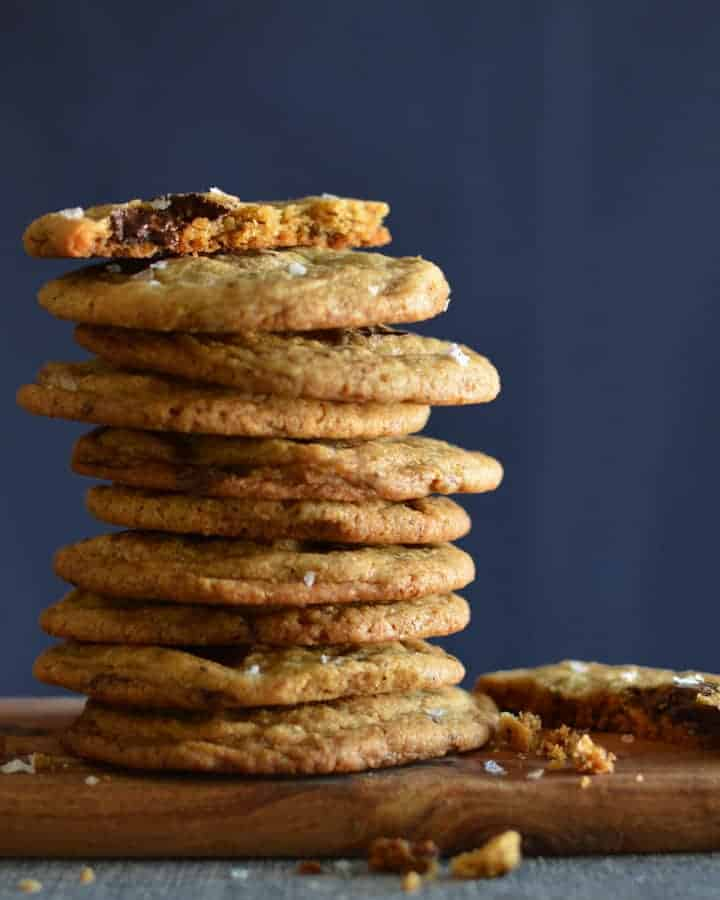 Stack of chocolate chip cookies on a board with blue background