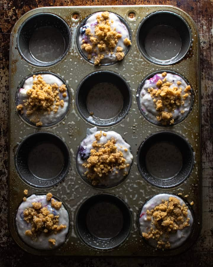 Unbaked muffin mix in pan with streusel before baking