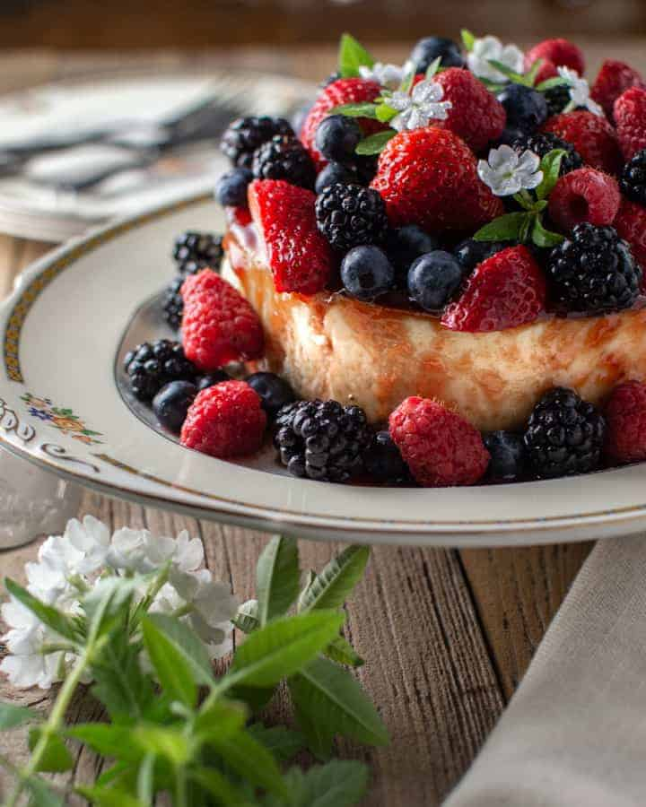 Summer berry topped cheesecake with white flowers on antique platter
