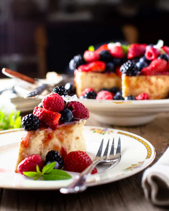 Mixed berry cheesecake slice with whole cake in background