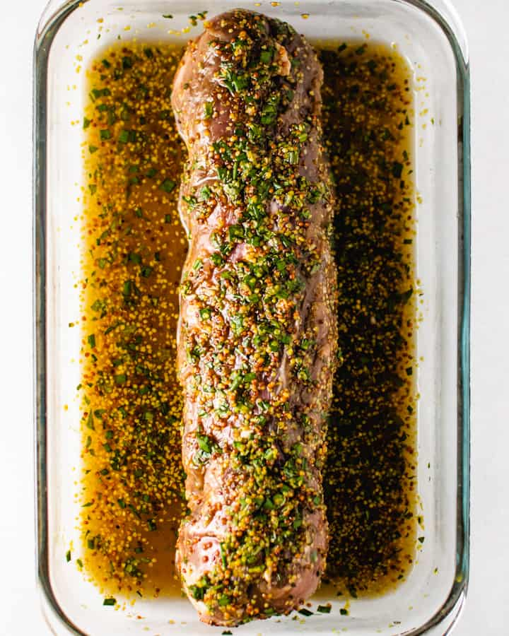 Raw pork tenderloin covered and sitting in marinade in rectangle glass dish