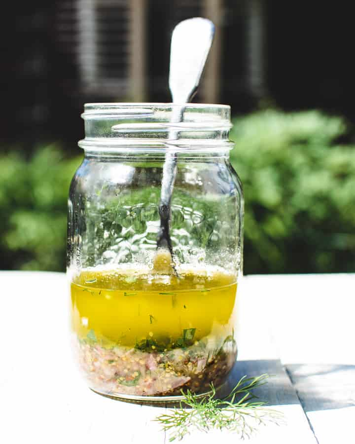 Mason jar with vinaigrette for Nicoise salad and fork.