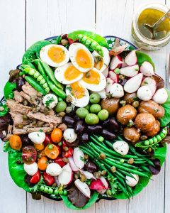 Nicoise salad with mixed vegetables, olives, tuna, boiled eggs with a dressing on the side on a round platter