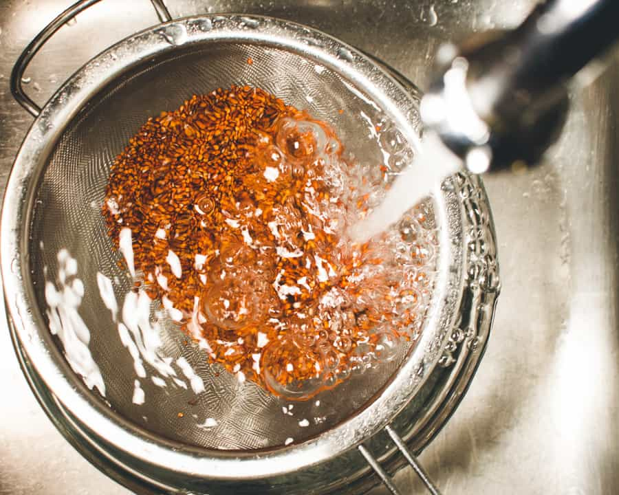 Red quinoa in a sieve under running water