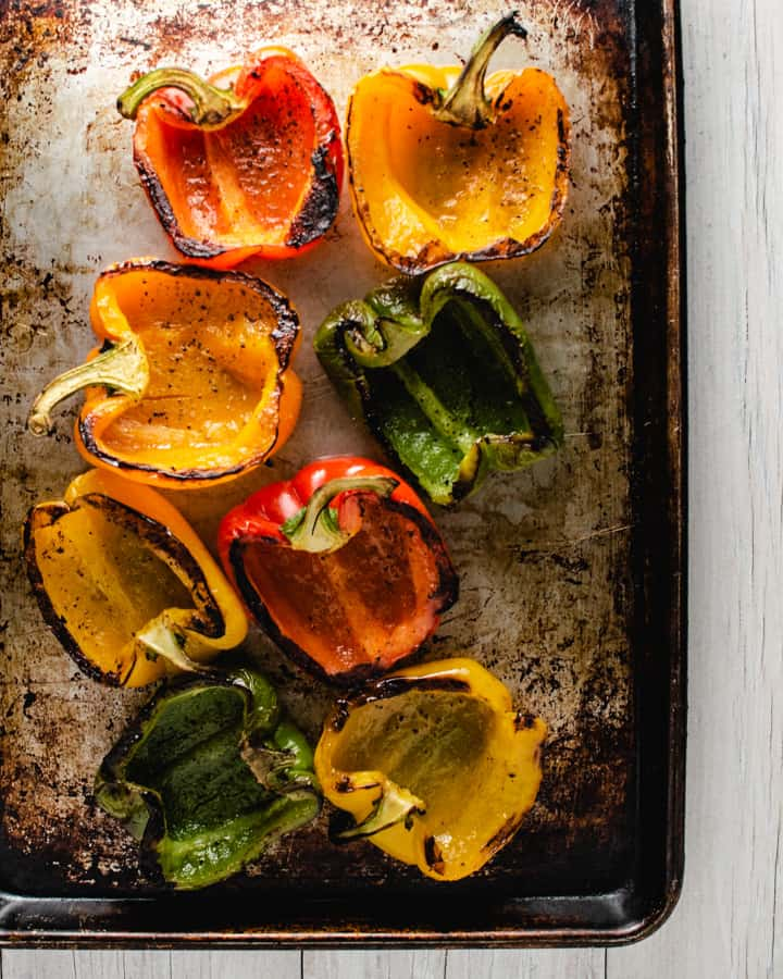 Charred peppers cut in half on a baking tray