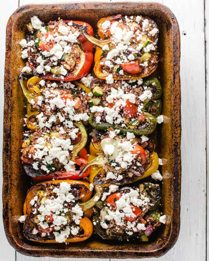 Baked stuffed peppers in clay dish with feta cheese sprinkled on top