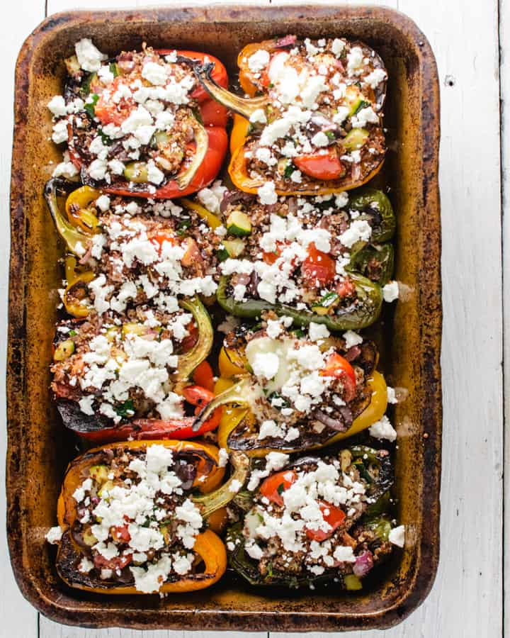 quinoa stuffed peppers in a clay baking dish sprinkled with feta cheese
