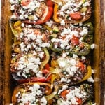 stuffed multi colored bell peppers in a clay baking dish with feta cheese