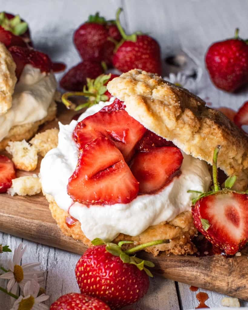 close up of a single strawberry shortcake on a wood board