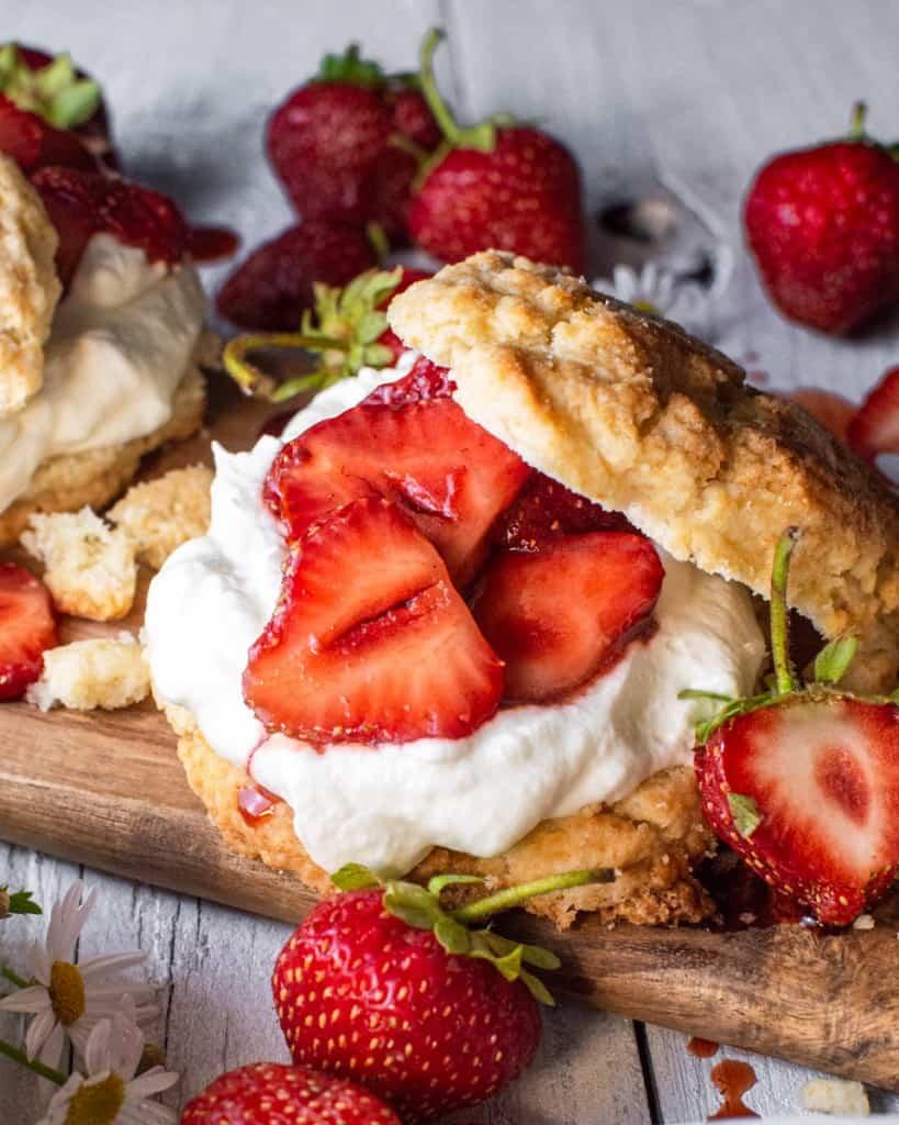 close up of a single strawberry shortcake on a wood board