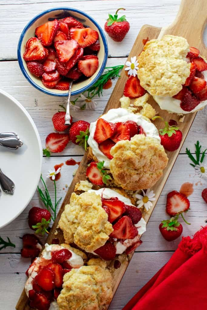 strawberry shortcakes with cream scones and balsamic strawberries with whipped cream assembled on a long board