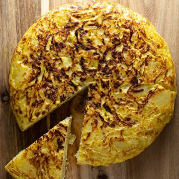 Spanish omelette on wood board with one slice slightly removed