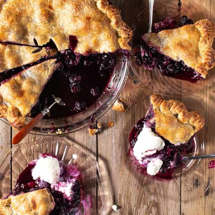 Blueberry Pie with 3 slices on plates with vanilla ice cream