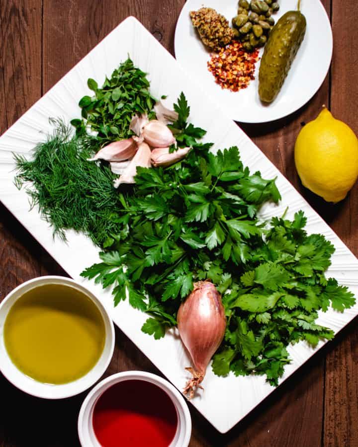 all ingredients for making salsa verde. fresh herbs, lemon, olive oil, mustard, capers, shallot, pickle and vinegar