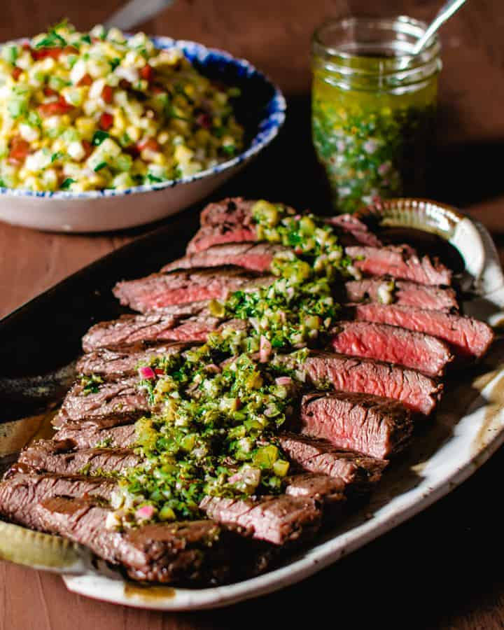 grilled flank steak with salsa verde on ceramic platter with corn salad and jar of salsa in the background