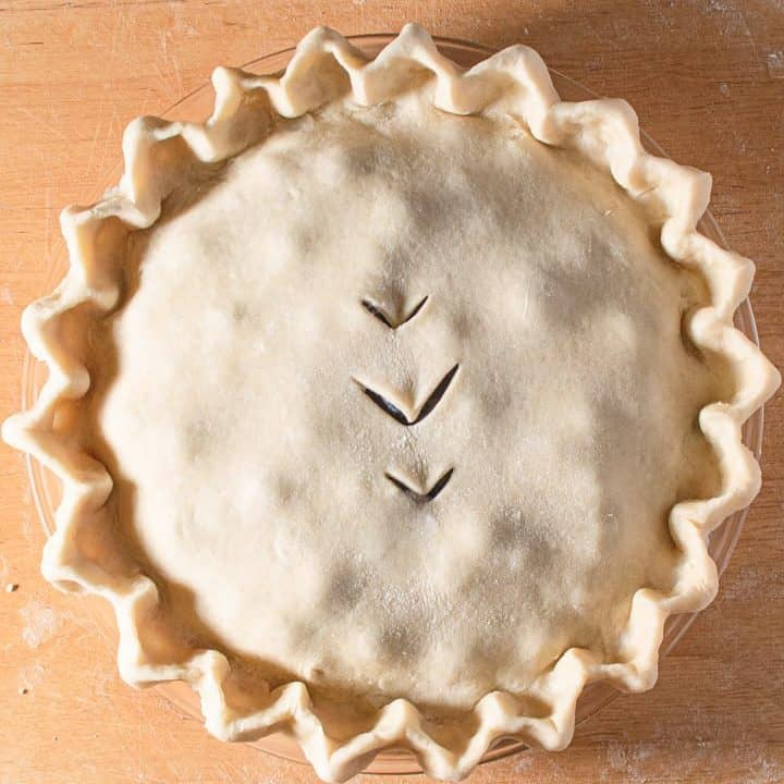 Raw double crust pie with crimped edges on a board