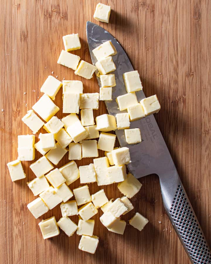 cubed butter with a chef's knife on wood board