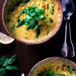 Brown pottery bowls with curried red lentil soup, 2 spoons, lemon and cilantro