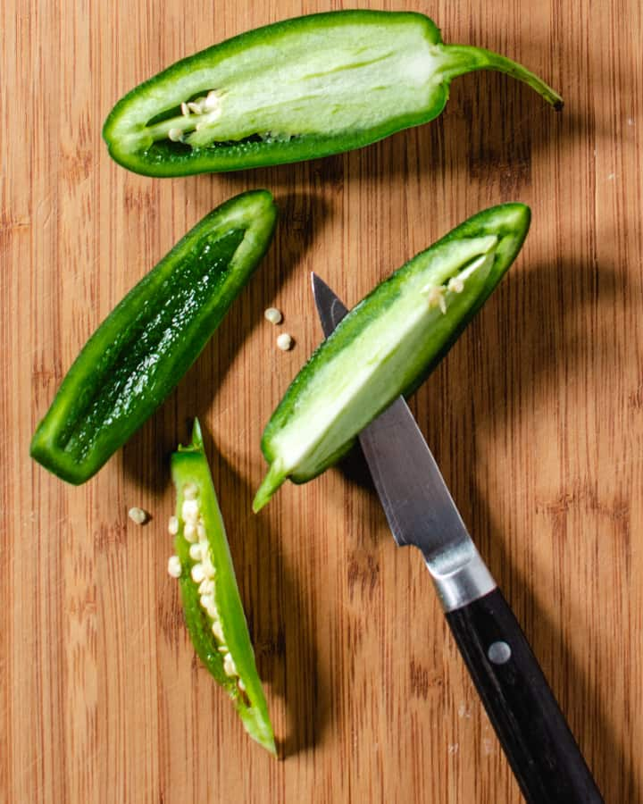 jalapeno peppers being cut on wood board