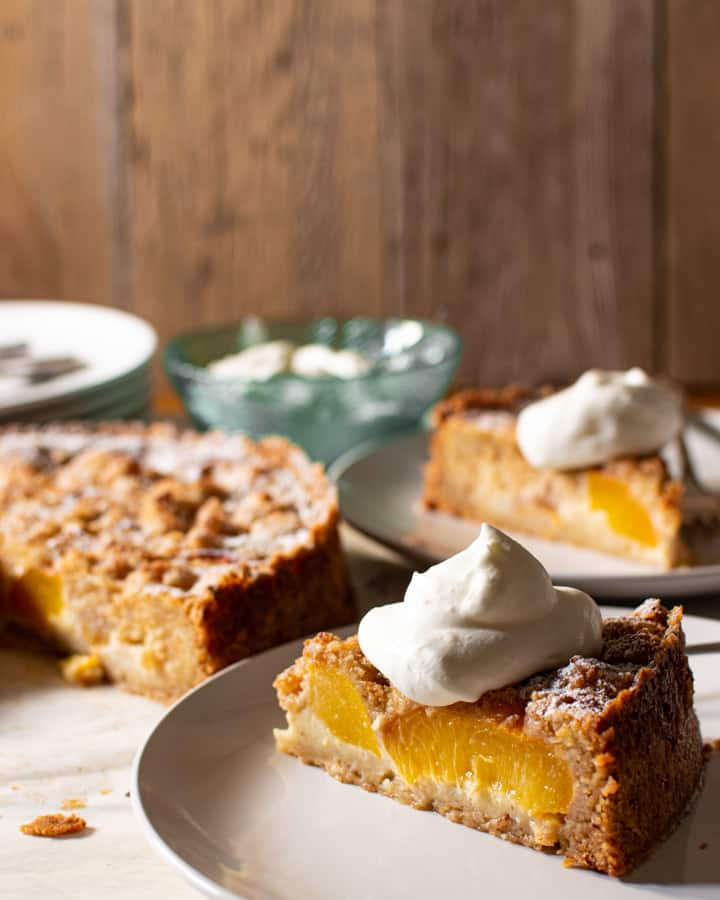close up slice of peach and almond tart with a dollop of whipped cream