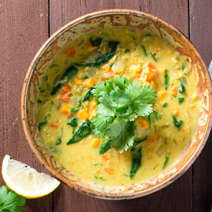 two bowls red lentil and vegetable soup with spoons, lemon slices and cilantro