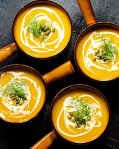 4 bowls of butternut squash fennel and apple soup with pumpkin seeds and frons as garnish. drizzled with cream