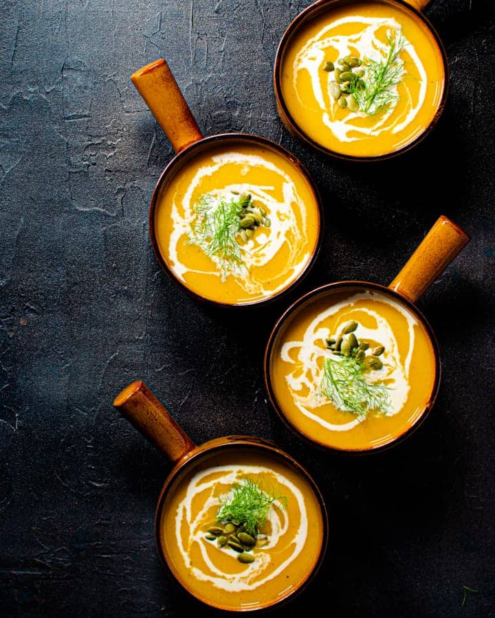 four bowls of butternut squash fennel and apple soup on a black background