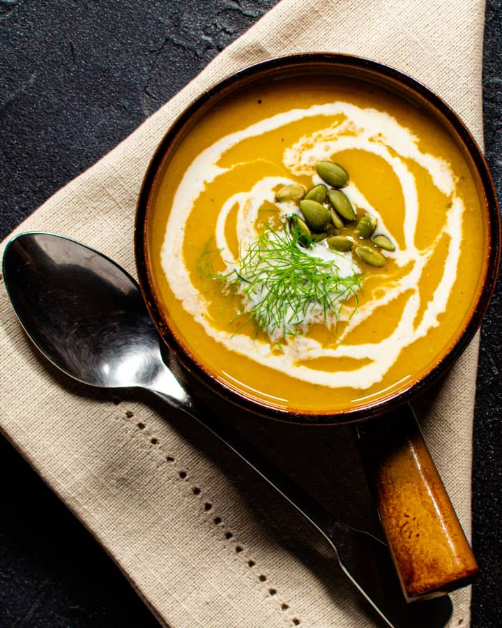 one bowl of squash fennel apple soup garnished with cream pumpkin seeds and fennel fronds