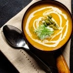 a bowl of butternut squash fennel and apple soup garnished with cream and pepitas on a napkin