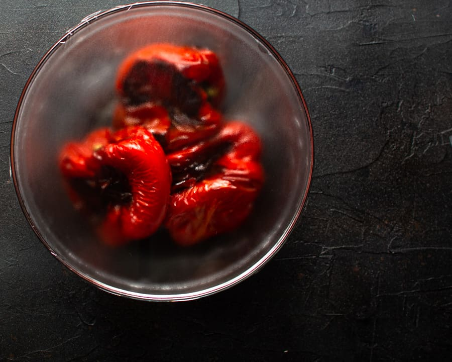 Roasted red peppers for Spanish chicken bake in glass bowl covered with plastic wrap.