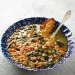 white bean sausage and arugula soup in blue bowl with Parmesan crostini and spoon
