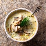 single bowl of creamy chicken and mushroom soup with spoon