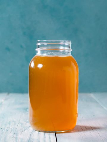 One liter mason jar of chicken stock with blue background