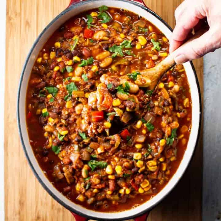 One pot of vegetarian 3 bean chili with wooden spoon being held to show ingredients