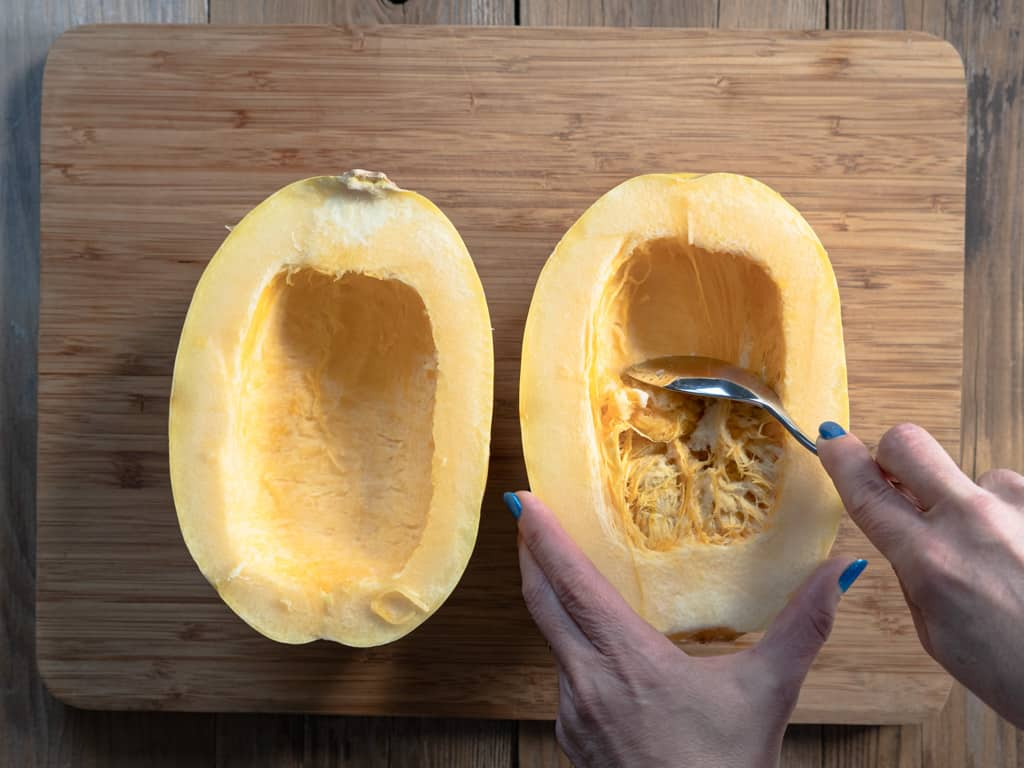 spaghetti squash cut in half with seeds being scraped out