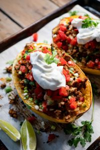 spaghetti squash stuffed with turkey taco filling topped with sour cream and tomaotes