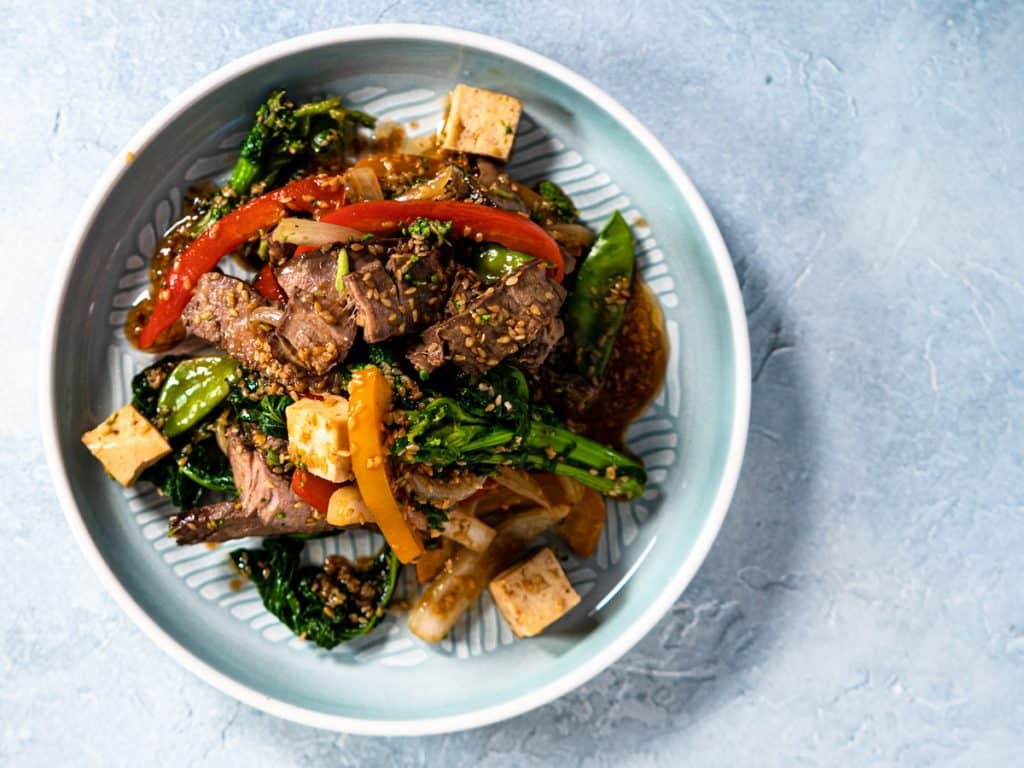 Beef stir fry on blue plate with blue background