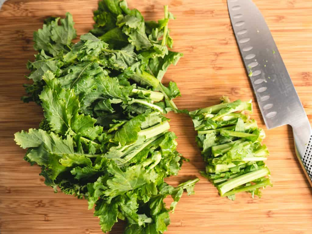 broccoli rabe with ends trimmed on a cutting board