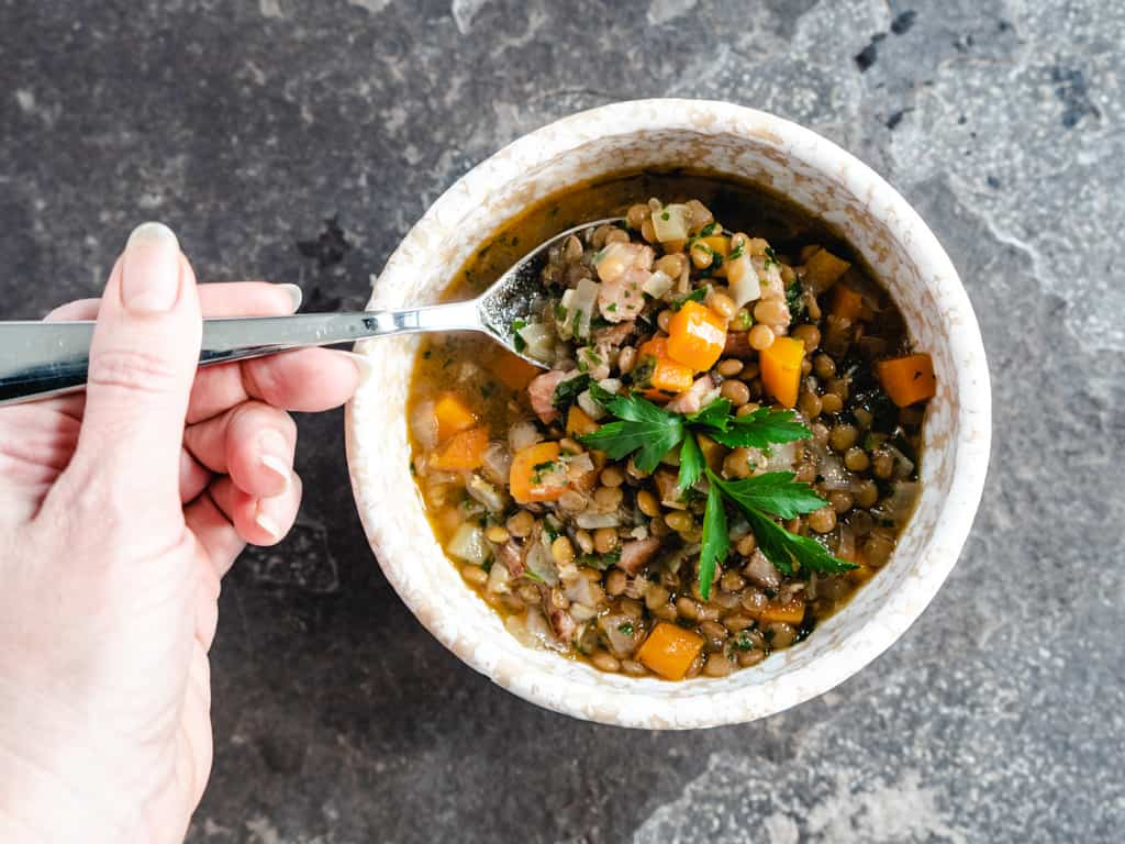 single bowl of lentil soup with a spoonful being picked up