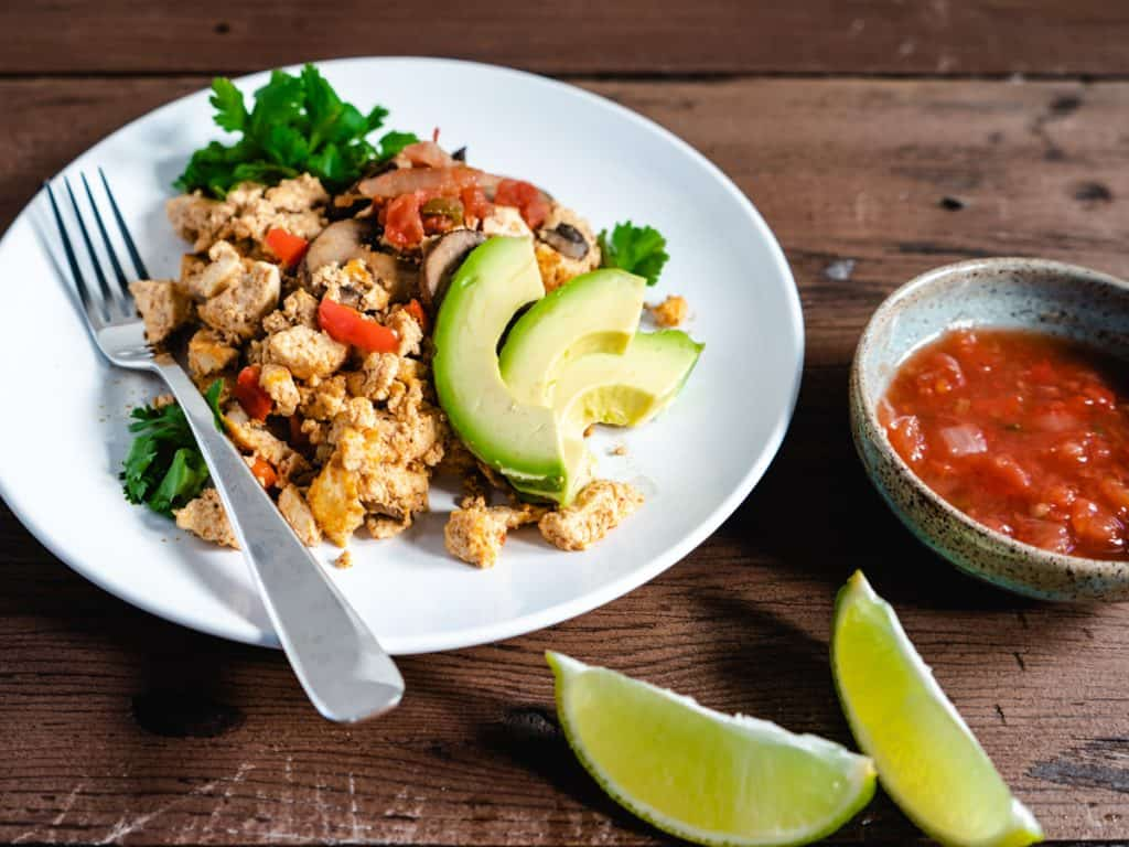 tofu scramble on white plate with avocado lime and salsa on the side