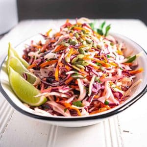 cumin lime coleslaw on white platter garnished with lime wedges