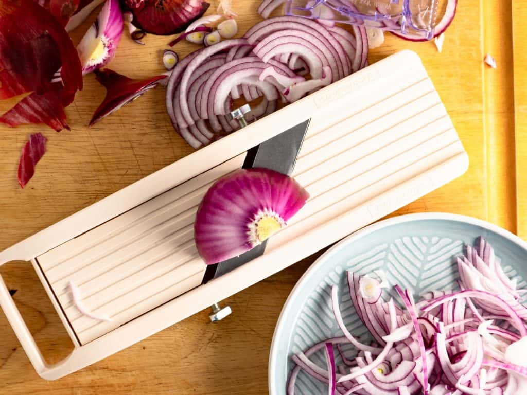 slicing red onion on a mandoline