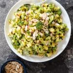 Roasted Broccoli salad on white plate with spoon on stone background
