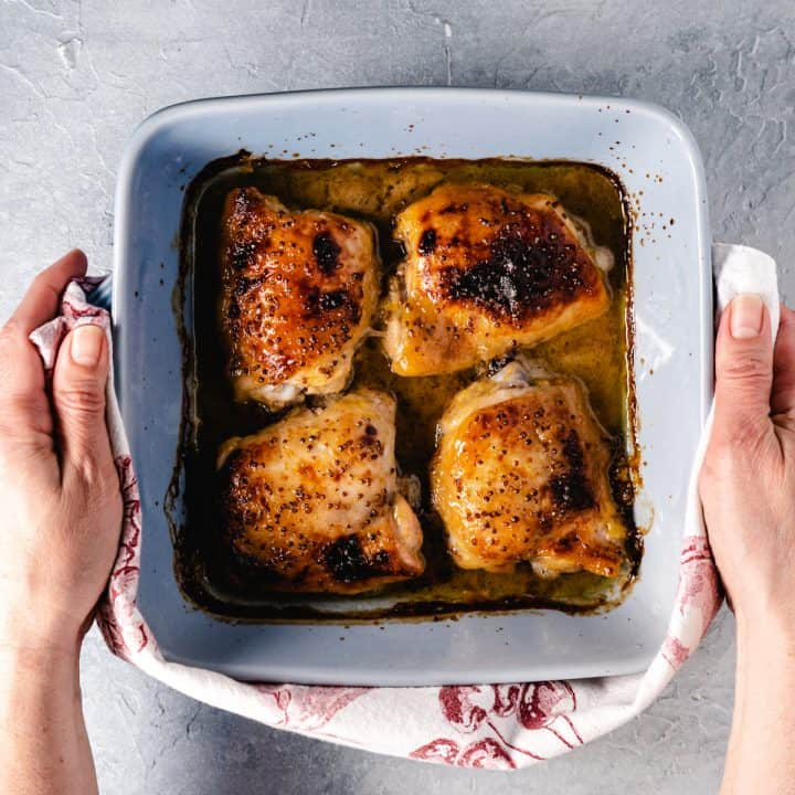 four baked chicken thighs in square blue dish being held with kitchen towel