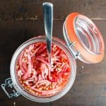 pickled onions in a jar with spoon