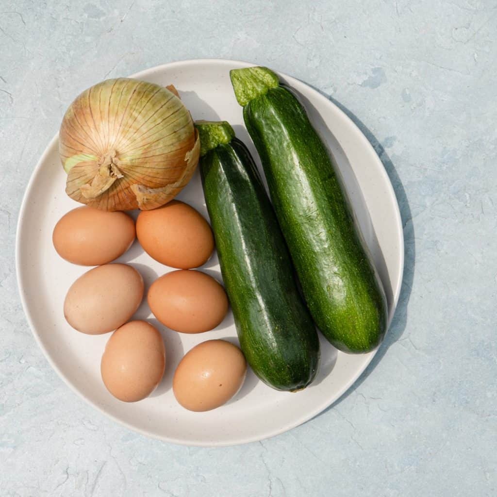 zucchini onion and eggs on white plate