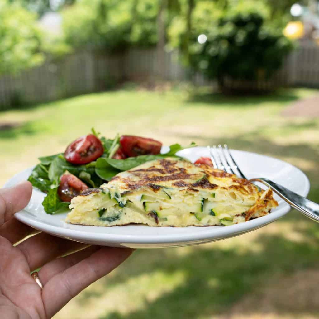 One slice of omelette with side salad on white plate