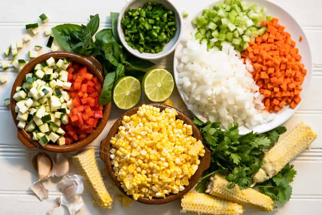 Prepared ingredients for chowder. Corn, onion, carrots, celery, red pepper, zucchini, garlic, basil, cilantro