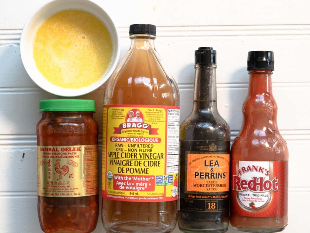 melted butter, sambal, apple cider vinegar, Worcestershire sauce and franks red hot sauce shown in their bottles