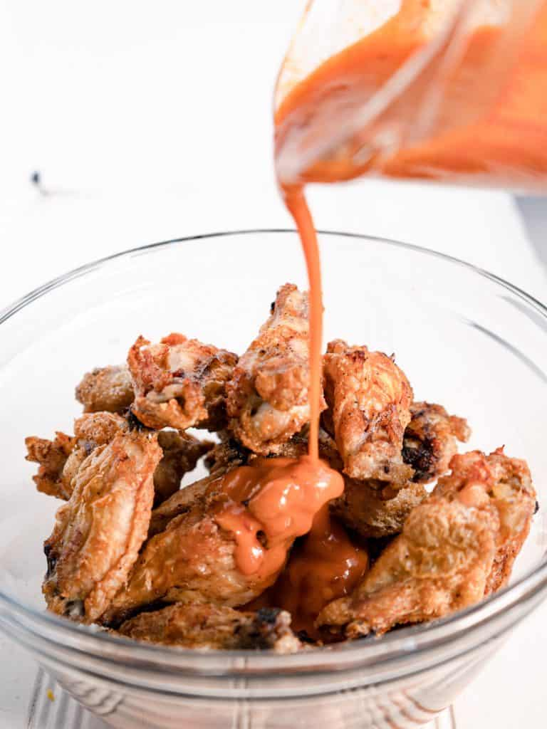 bowl of wings with sauce being poured over